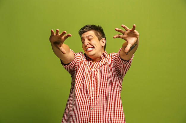 Krzyczenie, nienawiść, wściekłość. płacz emocjonalny zły człowiek krzyczy na tle zielonym studio. emocjonalna, młoda twarz. portret mężczyzny w połowie długości.