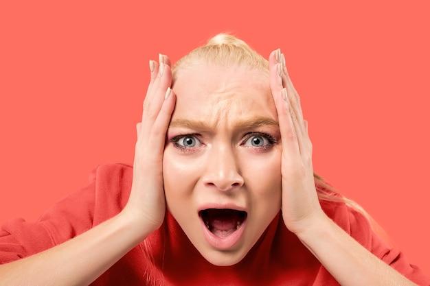 Krzyczenie, nienawiść, wściekłość. płacz emocjonalny zły kobieta krzyczy na tle koralowego studia. emocjonalna, młoda twarz. portret kobiety w połowie długości.