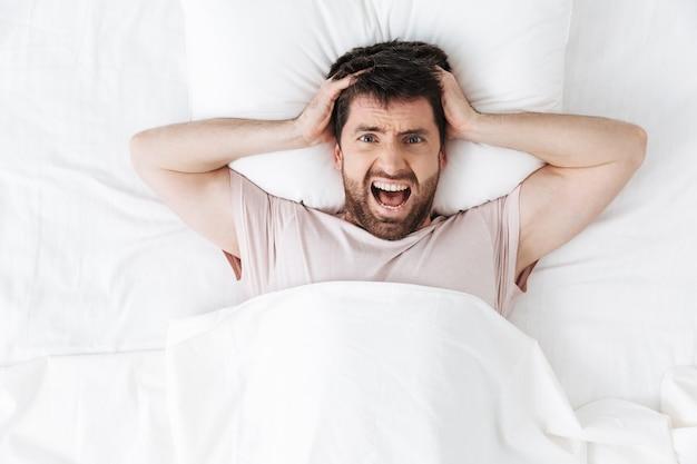 Krzyczy niezadowolony młody człowiek rano pod kocem leży w łóżku
