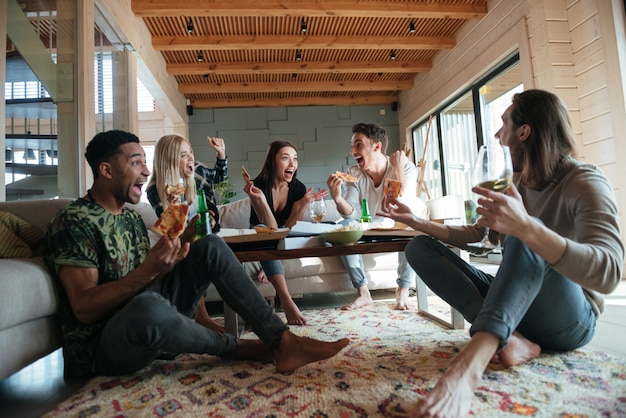Krzyczy pięciu przyjaciół siedzi w domu i je pizzę