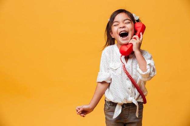 Krzyczy podekscytowany dziewczynka dziecko rozmawia przez czerwony telefon retro.
