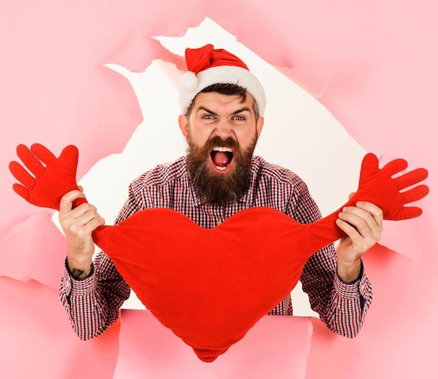 Krzyczy santa man z poduszką w kształcie serca. brodaty mężczyzna w santa hat z czerwoną poduszką w kształcie serca.