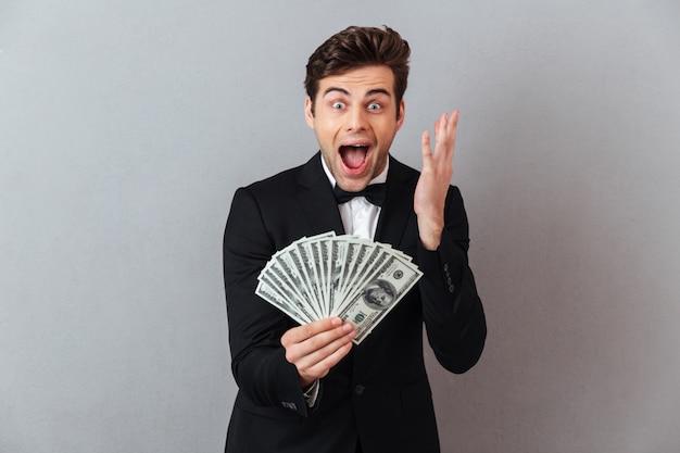 Krzyczy szczęśliwy człowiek w oficjalnym garniturze gospodarstwa pieniądze.