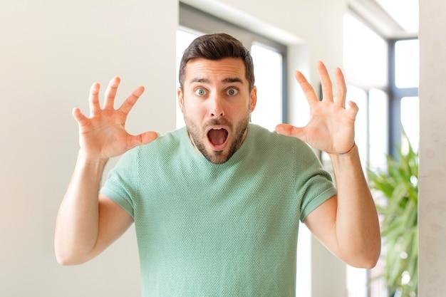 Krzyczy w panice lub złości, zszokowany, przerażony lub wściekły, z rękami przy głowie