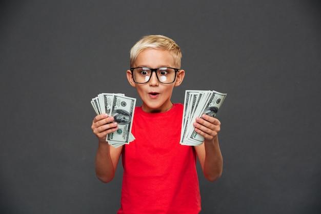 Krzyczy zaskoczony mały chłopiec dziecko pokazując pieniądze.
