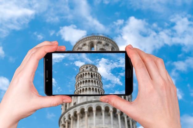 Krzywa wieża w pizie na zachmurzone niebo niebieskie. zdjęcie zrobione telefonem