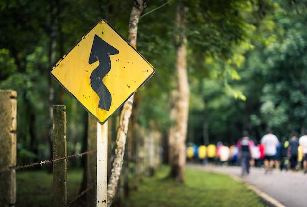 Krzywa znak ruchu i niewyraźne ludzi chodzących na drodze