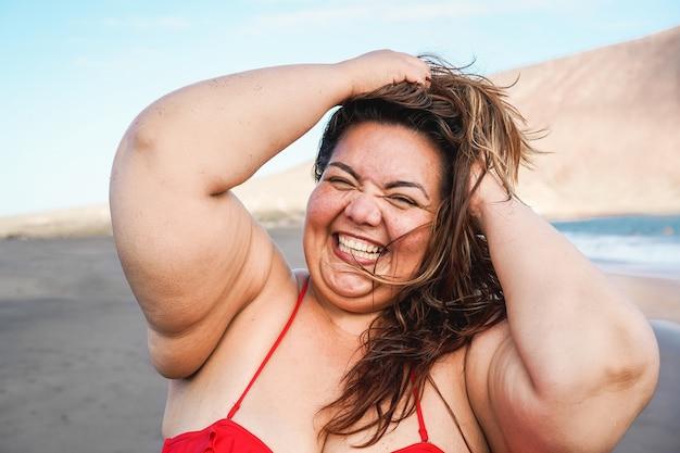 Krzywego kobieta uśmiecha się do kamery na sobie bikini z plażą w tle - plus rozmiar i nadwaga koncepcja kobiecego ciała