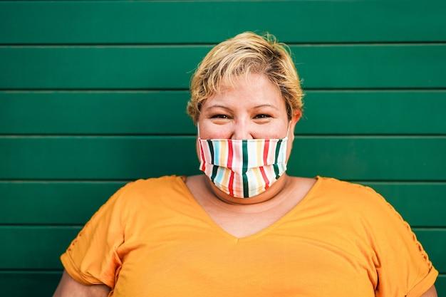 Krzywego kobieta uśmiecha się do kamery podczas noszenia maski ochronnej twarzy na zewnątrz