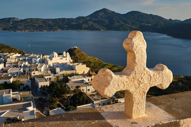 Krzyż chrześcijański i wioska plaka na wyspie milos nad czerwonymi kwiatami geranium o zachodzie słońca w grecji