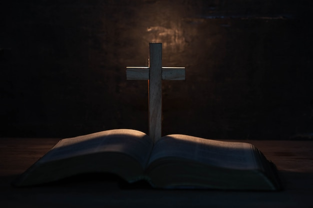 Krzyż i pismo święte na drewnianym stole