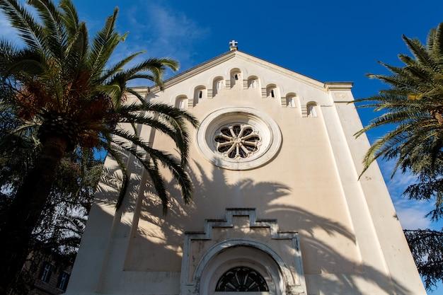 Krzyż na dachu kościoła z pomarańczowymi dachówkami na tle nieba w czarnogórze