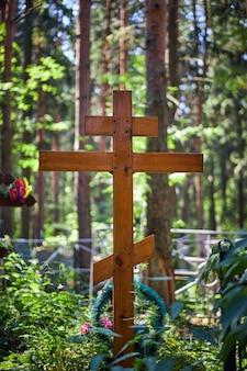 Krzyż na grobie, pochówek na cmentarzu. drewniany krzyż w świetle słonecznym