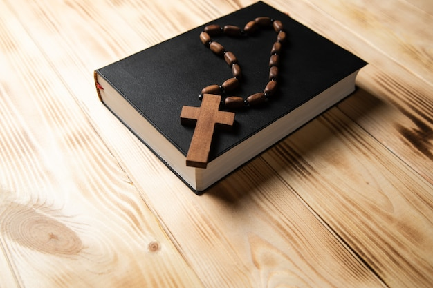 Krzyż na książce na drewnianym stole