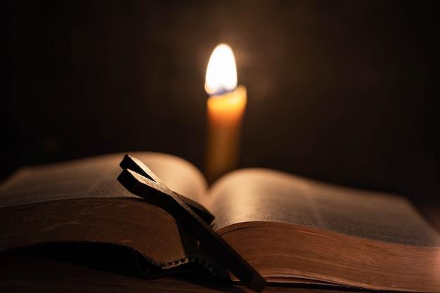 Krzyż z biblią i świecą na starym dębowym drewnianym stole.