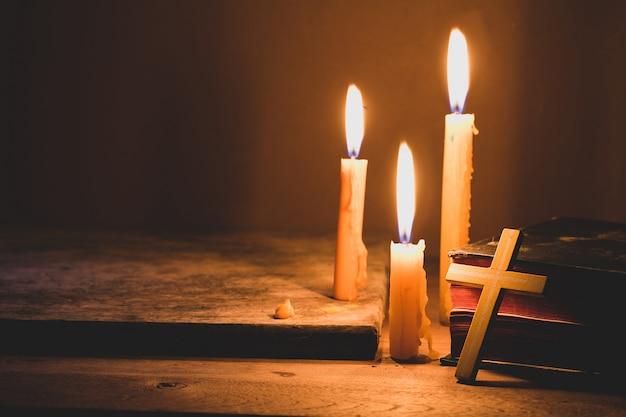 Krzyż z biblii i świeca na starym drewnianym stole dębu. piękne złote tło.