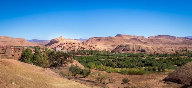 Ksar z ait-ben-haddou otoczony zielenią w słońcu i błękitnym niebem w maroku