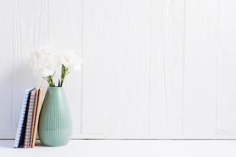 Książki blisko świeżych kwiatów w wazonie przeciwko malowane drewniane białe tapety