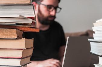 Książki w pobliżu człowieka z laptopem