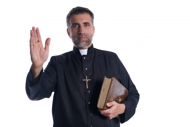 Ksiądz męskiej błogosławieństwo rękę z świętą biblię