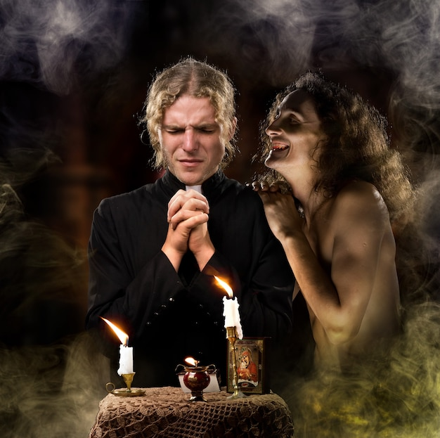 Ksiądz modli się z zapalonymi świecami