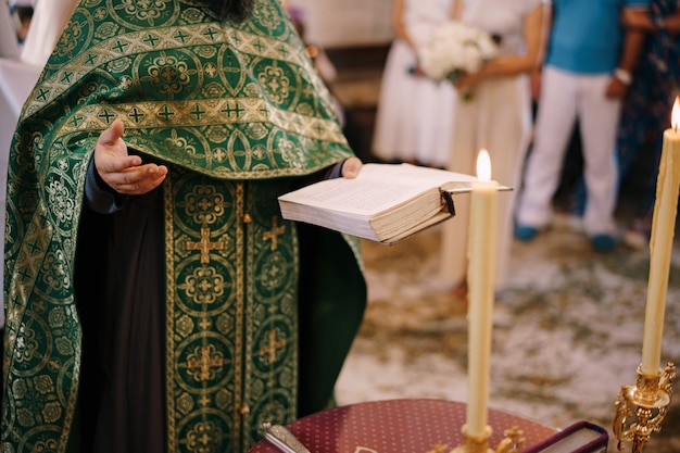 Ksiądz na weselu trzyma w ręku biblię