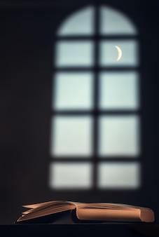 Książka (biblia, koran) na stole naprzeciw dużego okna i półksiężyca
