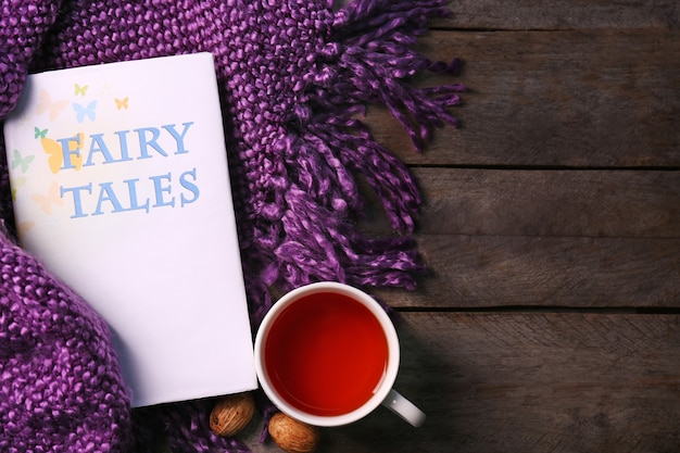 Książka, filiżanka herbaty i miękki koc na drewnianym stole