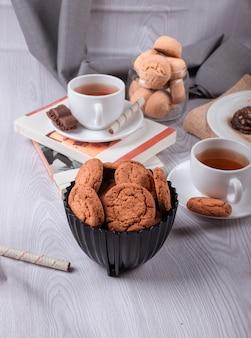 Książka, filiżanka herbaty i słodkie przekąski