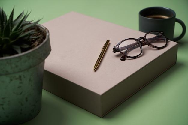 Książka, filiżanka kawy, okulary do czytania, długopis i ołówki na zielono