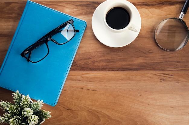 Książka glasseson z filiżanką kawy i lupą na stole