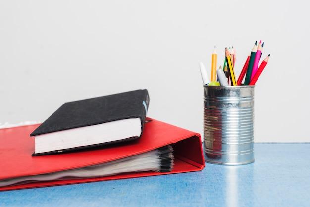 Książka i folder w pobliżu materiałów piśmiennych