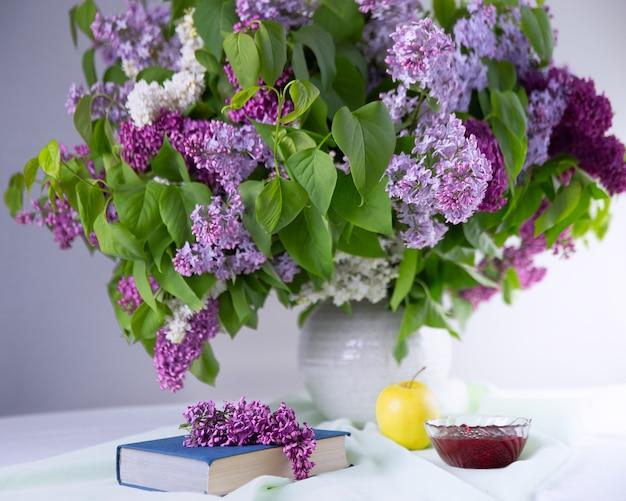 Książka i herbata oraz duży bukiet kwiatu bzu