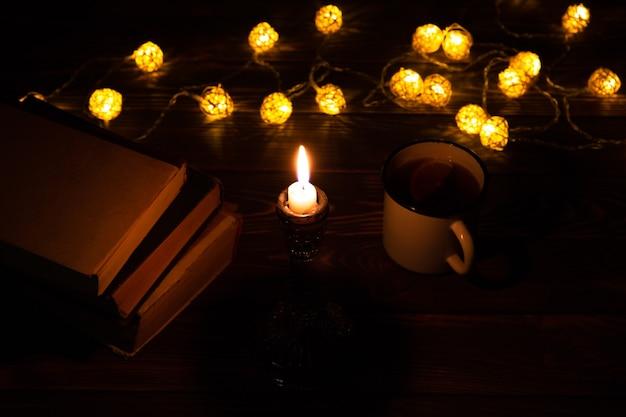 Książka i kubek gorącej herbaty na przytulny wieczór. świąteczny nastrój zdjęcie z bożonarodzeniowymi lampkami. drewniane serce i świeca. koncepcja hygge. idealny jesienny układ płaski.