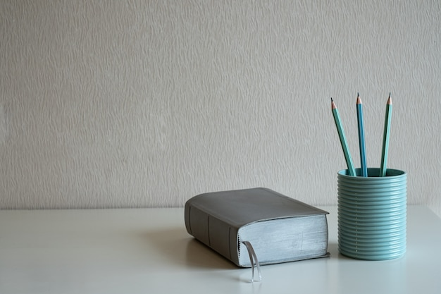 Książka i pastelowe ołówki w niebieskim szkle na biurku na szarym tle ściany