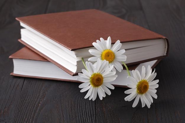 Książka i stokrotka kwiat na drewnianym stole