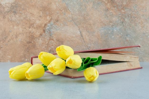 Książka i sztuczne tulipany na marmurowym tle. zdjęcie wysokiej jakości