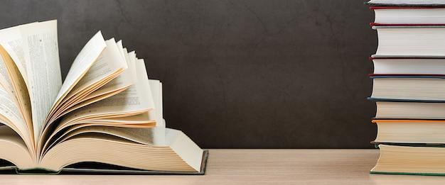 Książka jest otwarta obok stosu książek