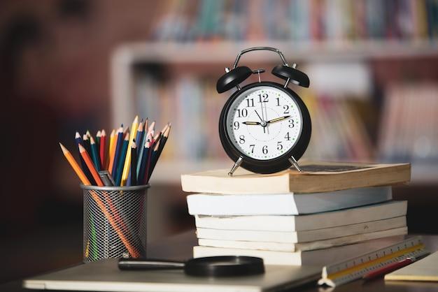 Książka, laptop, ołówek, zegar na drewnianym stole w bibliotece, edukaci uczenie pojęcie