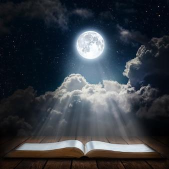 Książka na stole pod nocnym niebem. elementy tego obrazu dostarczone przez nasa