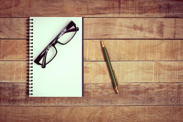 Książka, okulary i długopis do pracy na drewnianym stole