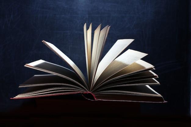 Książka. otwarta magiczna księga, książka na ciemnym tle