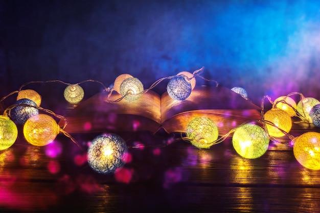 Książka. otwarta magiczna księga z magicznym światłem. abstrakcjonistyczna magiczna książka na drewnianym tle.
