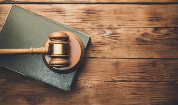 Książka prawnicza z drewnianym młotkiem sędziowskim na stole