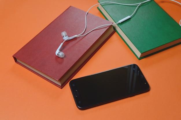 Książka, smartfon, słuchawki na pomarańczowym tle. audiobook. hobby. czas wolny. rekreacja. literatura.