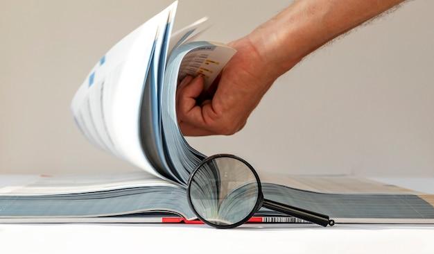 Książka techniczna z przewracaniem stron i badaniami inżynierów lupy