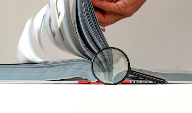 Książka techniczna z przewracaniem stron męskiej ręki i koncepcją badań i badań inżyniera soczewek powiększających