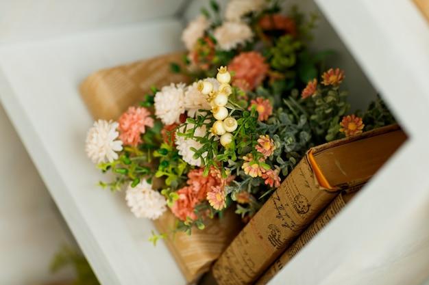 Książka w brązowej okładce na drewnianej półce z pięknymi wiosennymi kwiatami