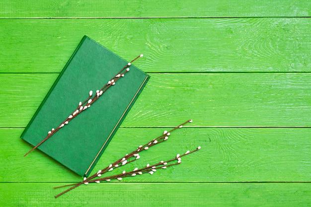 Książka w twardej zielonej okładce na zielonych gałęziach drewnianych i wierzbowych. copyspace