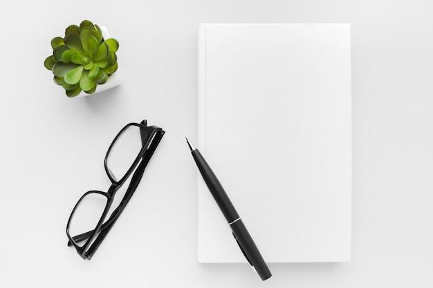 Książka z długopisem i okularami
